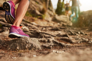 50988677 - close up of an athlete's feet wearing sports shoes on a challenging dirt track. trail running workout on rocky terrain outdoors.